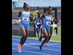 Tina Clayton (left) looks over at her twin sister Tia (right) as they cross the finish line in the  100 metres ahead of Thennel Williams (right) and Kacy-Ann Johnson (second left) during the JAAA All Comers meet at the National Stadium last Saturday. Tina won the race in 11.71 seconds.