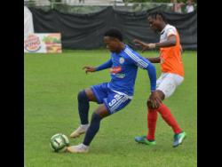 Mount Pleasant's Kemar Beckford (left) shielding the ball from Adrian Williams of Dumbeholden during a Jamaica Premier League match on Wednesday, January 16, 2019.