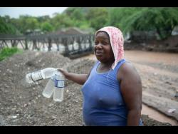Corrol Jolly looks to fill these plastic bottles with water after two pipes in 11 Miles were damaged by flood waters.
