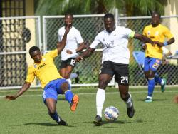 Cavalier's captain Kamoy Simpson (right) powering past Harbour View's Cristojaye Daley during yesterday's Jamaica Premier League match at the UWI/Captain Horace Burrell Centre of Excellence.  The game ended 1-1.