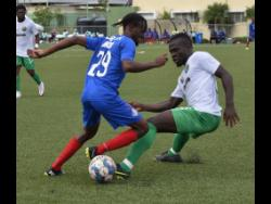 Tajay Brown (left) of Portmore United getting the better of  Vere United's Alton Lewis during  a Jamaica Premier League match at the UWI/Captain Horace Burrell Centre of Excellence yesterday. Vere won 1-0.