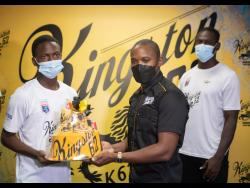 Cavalier's Dwayne Atkinson (left) accepts a Kingston 62 gift package from Kamal Powell,  Regional Marketing Manager, J. Wray and Nephew Limited, at the Jamaica Football Federation head office in New Kingston yesterday. Looking on at right is Cavalier's Kamoy Simpson.