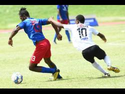 Dunbeholden's Shevan James (left) getting away from Dwayne Atkinson of Cavalier during yesterday's Jamaica Premier League match at the Stadium East field.