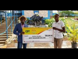 Guys Hill High School sixth-form student Nathan Douglas (right) accepts a cheque for $50,000 towards his educational welfare from TV talk show host and SAINT international CEO Deiwght Peters. Douglas recently appeared on Peters's show on TVJ which spotlighted Douglas's enterprising efforts to secure a construction site job to assist in paying for his online schooling. Prime Minister Andrew Holness also presented a $50,000 monetary gift to Douglas through his Positive Jamaica Foundation.