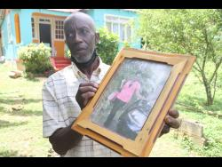 A distraught Ean Richards shows a photograph of his daughter, Annakaye Richards, who was murdered last Friday in her home in Comfort, Manchester.