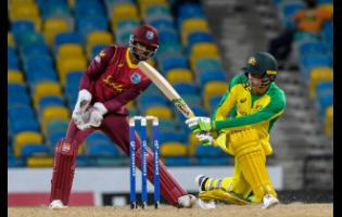 Australia batsman Alex Carey (right) plays a shot while West Indies wicketkeeper Shai Hope looks on during their third and final one-day international, at the Kensington Oval in Bridgetown, Barbados, yesterday.