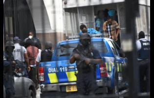 Alleged members of the Clansman gang being escorted to the Home Circuit Cout in downtown Kingston for their trial on Monday.