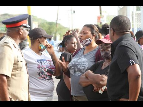 These persons get the ears of a senior policeman as they protest an incident that led to the deaths of three youngsters and the injuring of five others in Lionel Town, Clarendon.