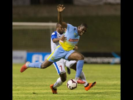 In this file photo from May 2019, Keithy Simpson (front), then of Waterhouse FC, is tackled by Portmore United's Damian Williams during a FLOW Concacaf Caribbean Club Championship match at the National Stadium in Kingston.