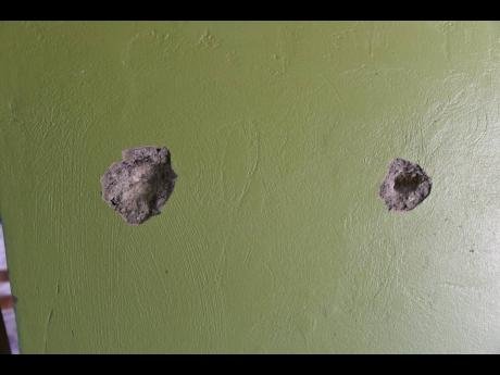 These bullet holes at an establishment in Cane River, Bull Bay, St Andrew, help to tell the story of Saturday night's shooting.