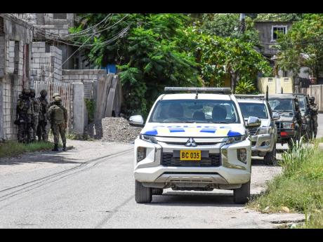 Members of the security forces patrol a section of Tavern, St Andrew yesterday.