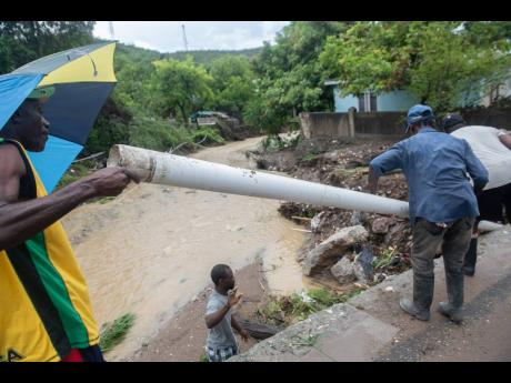 Residents of 11 Miles, Bull Bay, with one of the broken pipes.
