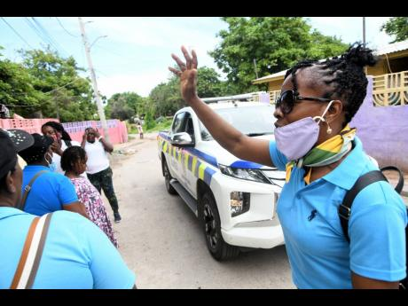 A woman prays on Monday for a family that came under a gun attack on Sunlight Street, Kingston 13, on Sunday. A baby was shot in the head.